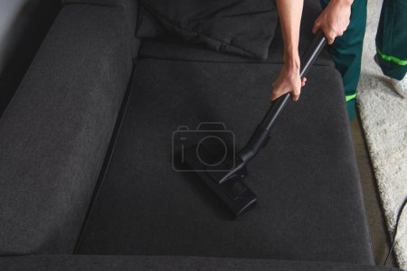high angle view of person cleaning furniture with vacuum cleaner, upholstery cleaning