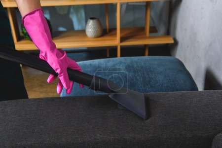 partial view of person in rubber glove cleaning furniture with vacuum cleaner