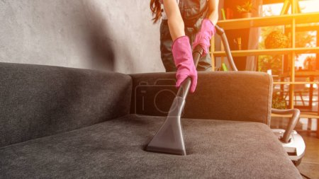Photo for Cropped shot of woman in rubber gloves cleaning sofa with vacuum cleaner - Royalty Free Image