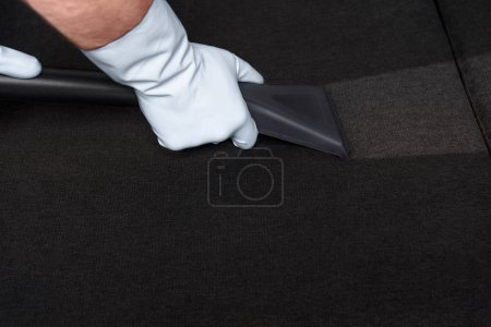 Photo for Close-up partial view of person in rubber gloves cleaning sofa with vacuum cleaner - Royalty Free Image