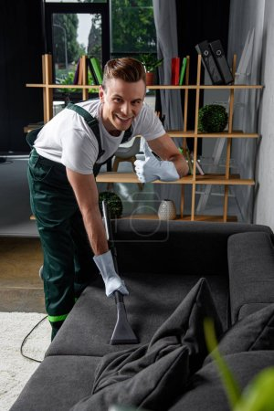 Photo for Smiling young cleaning company worker cleaning sofa with vacuum cleaner and showing thumb up - Royalty Free Image