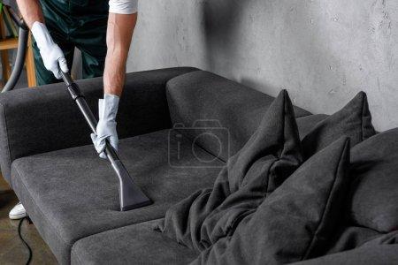 Photo pour Recadrée tir de l'homme dans des gants de caoutchouc à l'aide de votre aspirateur et nettoyage canapé - image libre de droit