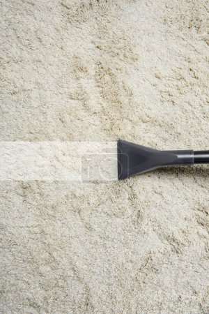 close-up view of cleaning white carpet with professional vacuum cleaner