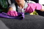 close-up view of woman in rubber gloves cleaning sofa with rag and detergent spray