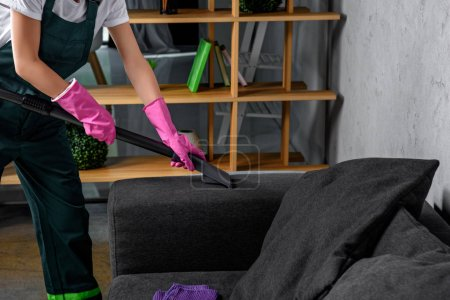 Photo for Cropped shot of person in rubber gloves cleaning sofa with vacuum cleaner - Royalty Free Image