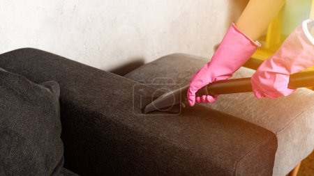 Photo for Close-up partial view of person in rubber gloves cleaning furniture with vacuum cleaner - Royalty Free Image