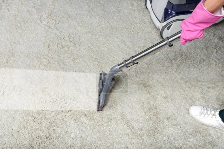 Photo for Cropped shot of person cleaning white carpet with vacuum cleaner - Royalty Free Image