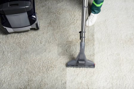 Photo for High angle view of person cleaning white carpet with professional vacuum cleaner - Royalty Free Image