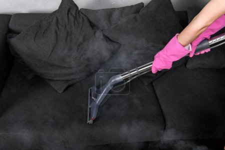 Photo for Cropped shot of person in rubber gloves cleaning sofa with vacuum cleaner and hot steam - Royalty Free Image