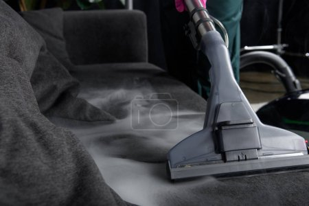 close-up view of person cleaning sofa with vacuum cleaner, hot steam cleaning concept