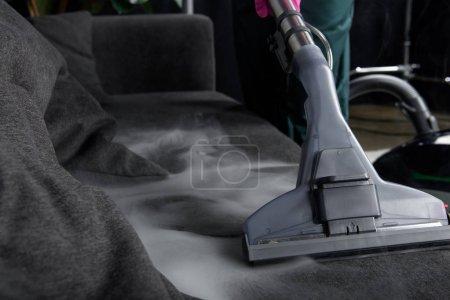 Foto de Vista cercana de persona limpieza sofá con aspiradora, caliente vapor limpieza concepto - Imagen libre de derechos