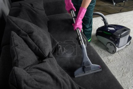 Photo for Cropped shot of person cleaning sofa with vacuum cleaner, upholstery cleaning concept - Royalty Free Image