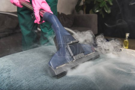 Photo for Cropped shot of person cleaning sofa with vacuum cleaner, hot steam cleaning concept - Royalty Free Image