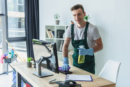 Photo for Handsome professional cleaner in rubber gloves holding detergent spray and smiling at camera in office - Royalty Free Image