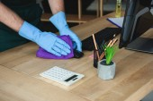 cropped shot of professional cleaner in rubber gloves cleaning computer mouse on office table