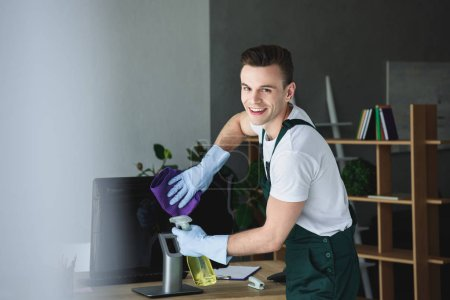 Photo for Handsome young professional cleaner smiling at camera while cleaning computer monitor in office - Royalty Free Image
