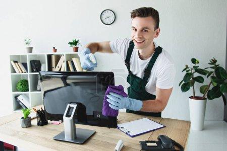 Foto de Guapo joven limpiador de guantes limpieza a monitor de la computadora y sonriendo a cámara - Imagen libre de derechos