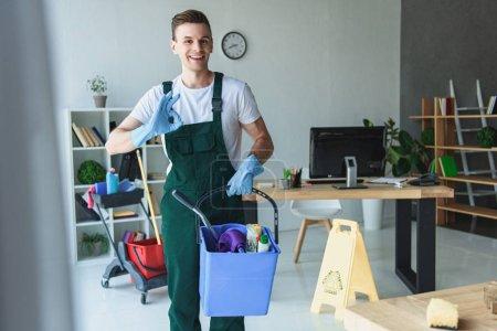 Photo pour Beau sourire nettoyeur jeune tenant seau avec fournitures de nettoyage et de montrer signe OK - image libre de droit