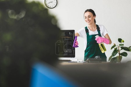 Photo for Selective focus of smiling young woman with spray bottle and rag cleaning computer monitor in office - Royalty Free Image