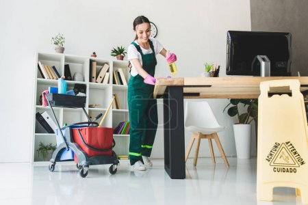 Photo for Low angle view of smiling young janitor cleaning modern office - Royalty Free Image