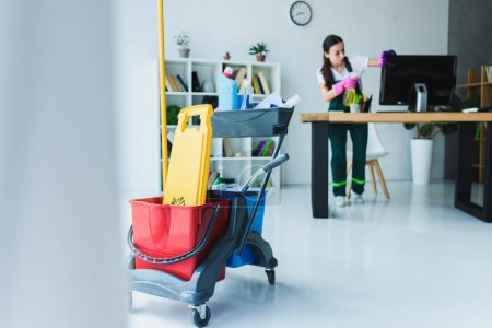 Photo for Young female janitor cleaning office with various cleaning equipment - Royalty Free Image