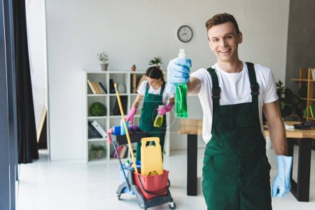 Photo for Young male cleaner in rubber gloves holding spray bottle with detergent and smiling at camera - Royalty Free Image