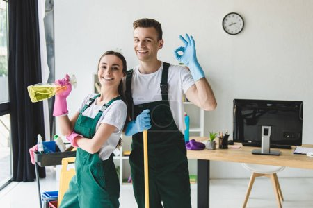 Photo for Happy young cleaning company workers holding cleaning equipment and showing ok sign - Royalty Free Image