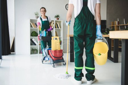 Photo for Cropped shot of young cleaners holding various cleaning equipment in office - Royalty Free Image