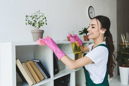 Photo for Smiling young woman in rubber gloves cleaning shelves in office - Royalty Free Image