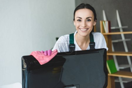 Photo for Attractive young woman cleaning computer monitor and smiling at camera - Royalty Free Image