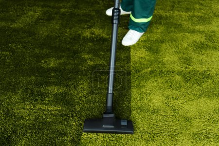 low section of person cleaning green carpet with vacuum cleaner