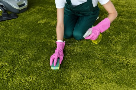 cropped shot of woman in rubber gloves cleaning carpet with rag and detergent spray