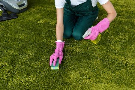 Foto de Recortar foto de mujer en guantes de goma, limpieza de alfombra con trapo y detergente spray - Imagen libre de derechos