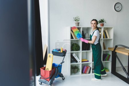 young cleaner holding duster and smiling at camera while cleaning shelves in office