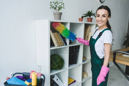 beautiful young cleaner holding duster and smiling at camera while cleaning shelves in office