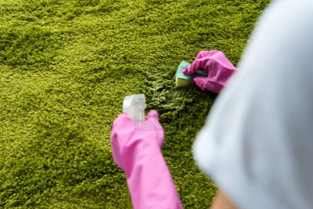 cropped shot of person in rubber gloves cleaning carpet with rag and detergent spray
