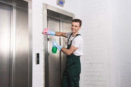 handsome young cleaner washing elevator and smiling at camera