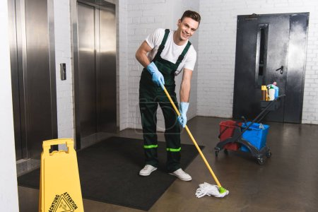 Photo for Handsome young janitor mopping floor and smiling at camera - Royalty Free Image