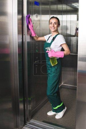 Foto de Hermosa joven conserje limpieza ascensor y sonriendo a cámara - Imagen libre de derechos