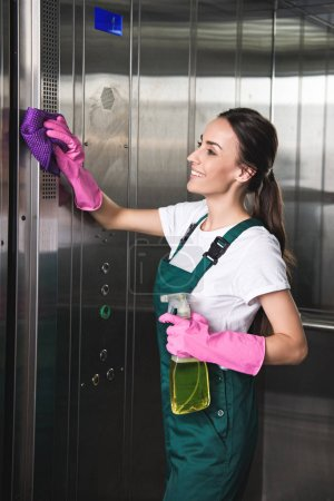 Photo for Beautiful smiling young cleaning company worker cleaning elevator with detergent and rag - Royalty Free Image