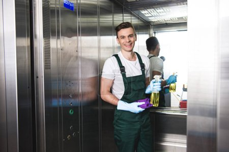 Photo for Handsome young janitor holding spray bottle with detergent and rag, smiling at camera in elevator - Royalty Free Image