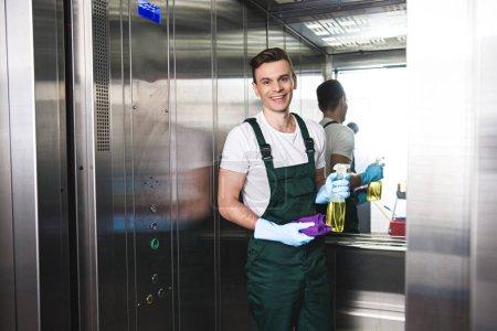 Foto de Portero joven guapo sosteniendo la botella de spray con detergente y trapo, sonriendo a la cámara en el ascensor - Imagen libre de derechos