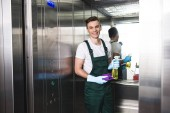 handsome young janitor holding spray bottle with detergent and rag, smiling at camera in elevator