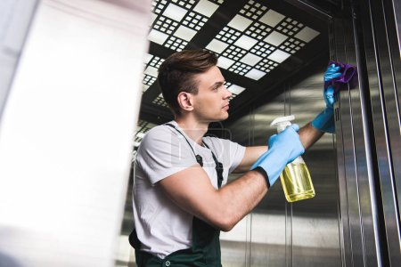 Photo for Low angle view of handsome young cleaner washing elevator with rag and detergent - Royalty Free Image