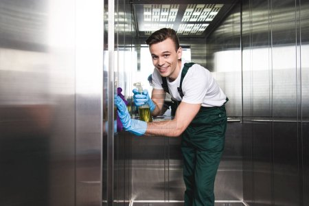 handsome young cleaning company worker cleaning elevator and smiling at camera