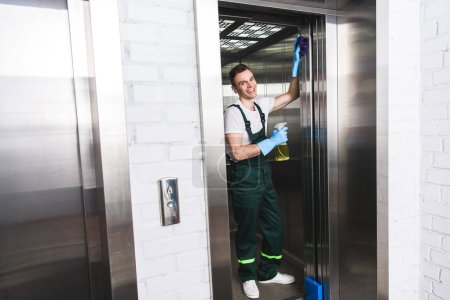 handsome young janitor cleaning elevator and smiling at camera
