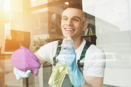 Photo for Handsome smiling young man cleaning and wiping window with spray bottle and rag - Royalty Free Image
