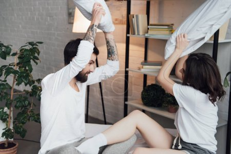 beautiful young couple in pajamas having fun and fighting with pillows at home