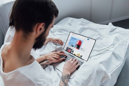 Photo for Back view of couple lying in bed, holding hands and using laptop with ebay website on screen - Royalty Free Image
