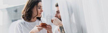 Photo pour Beau jeune couple buvant le café en matinée et en regardant l'autre - image libre de droit